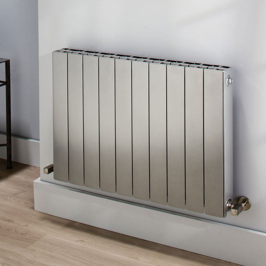gray square edged wall mounted hydronic radiator mounted on a gray wall with hard wood floors
