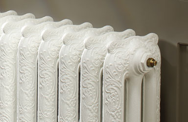 off white embossed cast iron radiator with carved pattern against a gray wall