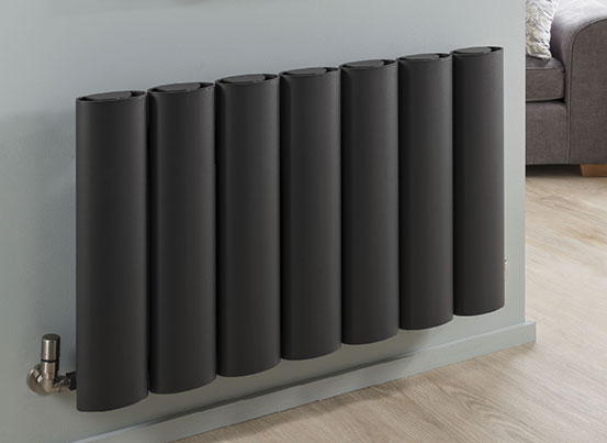 gray ovali tubular radiator mounted on a blue wall below two artworks