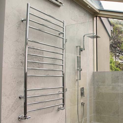 metal delonghi iconic heated towel rail mounted on a stone wall