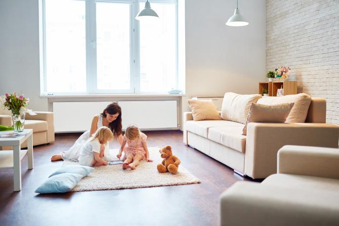 two children play with their mother on a rug in front of a white radiant heater