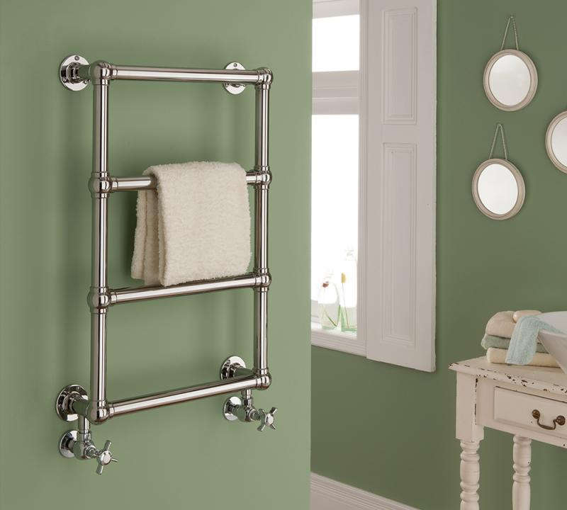 metal chalfont heated towel rail mounted on a green bathroom wall